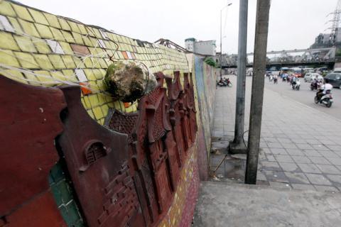 Hòn đá giữ bạt che mưa nắng của một quầy hàng trong chợ Long Biên được treo cố định trên mặt bức tranh ghép sứ.