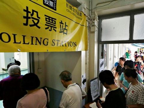 Xếp hàng tại một điểm bỏ phiếu để bỏ phiếu cho một cuộc trưng cầu dân ý không chính thức về cải cách dân chủ tại Hong Kong.
