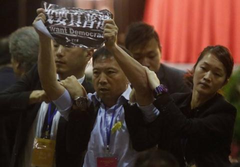 Nghị sĩ Wu Chi-wai, thuộc Đảng Dân chủ ở Hồng Kông, bị an ninh kềm chặt khi ông giương biểu ngữ trong buổi nói chuyện của phó tổng thư ký Ủy ban Thường vụ Quốc hội Trung Quốc