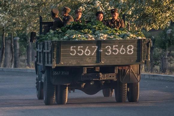 Các quân nhân Triều Tiên ngồi sau thùng xe chất đầy rau cải thảo.