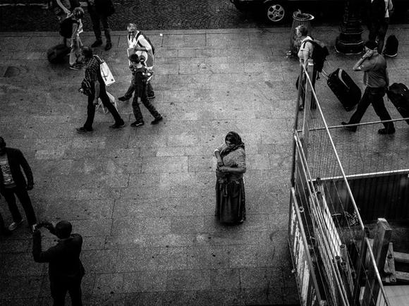 Một người phụ nữ đang xin tiền bên ngoài Gare du Nord. Công việc đại tu nhà ga vừa mới bắt đầu sau nhiều tháng dọn dẹp bụi bặm và phân chim bồ câu.