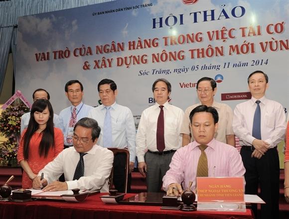 Ông Nguyễn Quang Minh - Giám đốc Vietcombank Tiền Giang (bên phải) và ông Nguyễn Văn Đôn - Giám đốc Công ty TNHH Việt Hưng ký hợp đồng vay vốn trước sự chứng kiến của Thống đốc NHNN Nguyễn Văn Bình và lãnh đạo các tỉnh Đồng bằng Sông Cửu Long