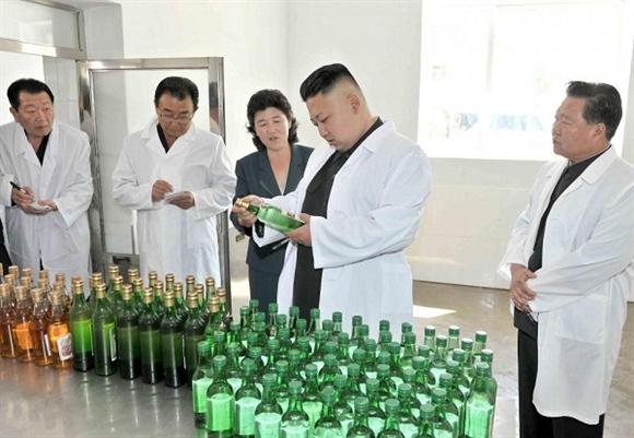 Nhà lãnh đạo Kim Jong-un kiểm tra các chai cồn khi thị sát Nhà máy Thực phẩm Changsong.