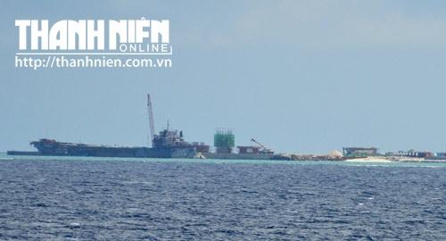 Hai cần cẩu khác đang phục vụ việc xây dựng các công trình khác ở giữa đảo, với khu vực tập kết cây xanh, chuẩn bị được trồng. Đằng sau tàu vận tải là công trình có thể là trung tâm kiểm soát không lưu - chỉ huy bay cũng đang được gấp rút xây dựng (khối nhà tròn, phủ ni lông màu xanh).