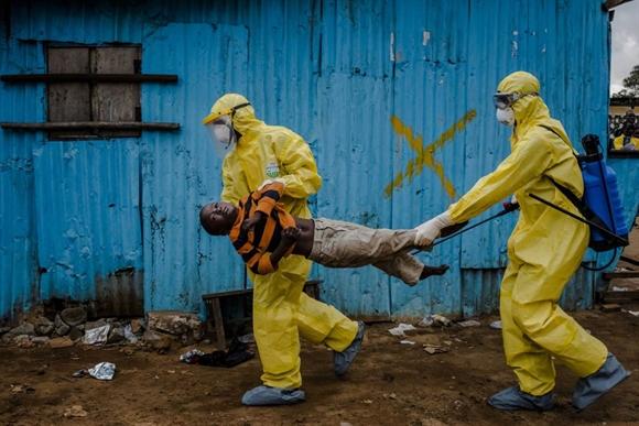 Nhân viên y tế di chuyển cậu bé 8 tuổi James Dorbor nhiễm Ebola tại Monrovia, Liberia hôm 5/9. Dù được chuyển tới trung tâm điều trị Ebola nhưng Dorbor tử vong vài ngày sau đó. Ảnh: NYtimes