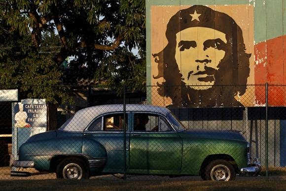Chiếc xe cổ đi ngang qua bích họa lãnh đạo Che Guevara ở Havana