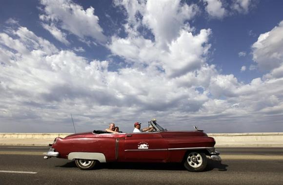 Khách du lịch trên chiếc Cadillac 1952 mui trần trên đại lộ ven biển El Malecon, Havana