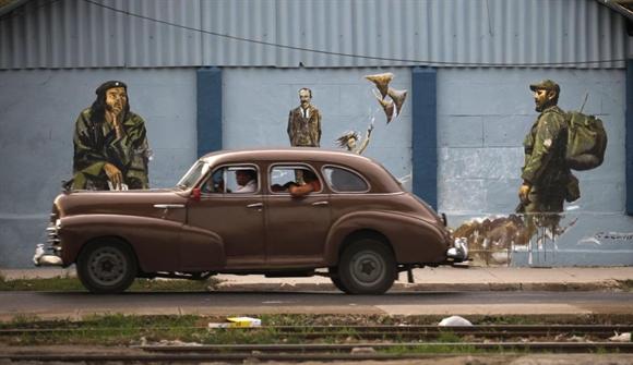 Chiếc xe cổ đi ngang qua bích họa lãnh đạo Fidel Castro, Jose Marti và Che Guevara ở Havana