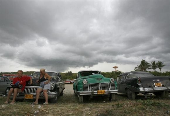 Hai người phụ nữ ngồi nghỉ bên những chiếc xe cổ bên bờ biển ở Guanabo