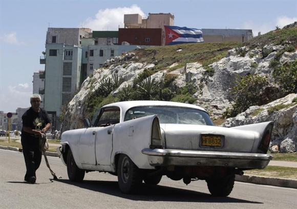 Người thợ máy đang sửa chiếc Chrysler 1958 trên một con phố ở Havana