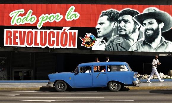 Chevrolet 1956 làm taxi đậu bên dưới bích họa cổ động đại hội Union de Jovenes Comunistas  (Liên minh Cộng sản Thanh niên) ở Havana