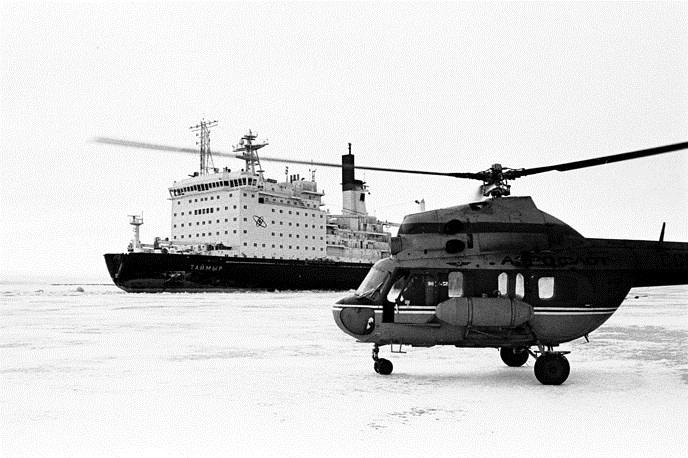 Hạm đội này bao gồm 4 tàu phá băng nguyên tử và 4 tàu dịch vụ hậu cần. Trong ảnh: Tàu phá băng nguyên tử Taimyr và trực thưang Mi-2 trên Cực Bắc. Nguồn ảnh: Tass.