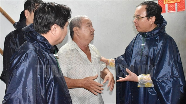 Ông Nguyễn Văn Nên dầm mưa khảo sát dự án chống ngập