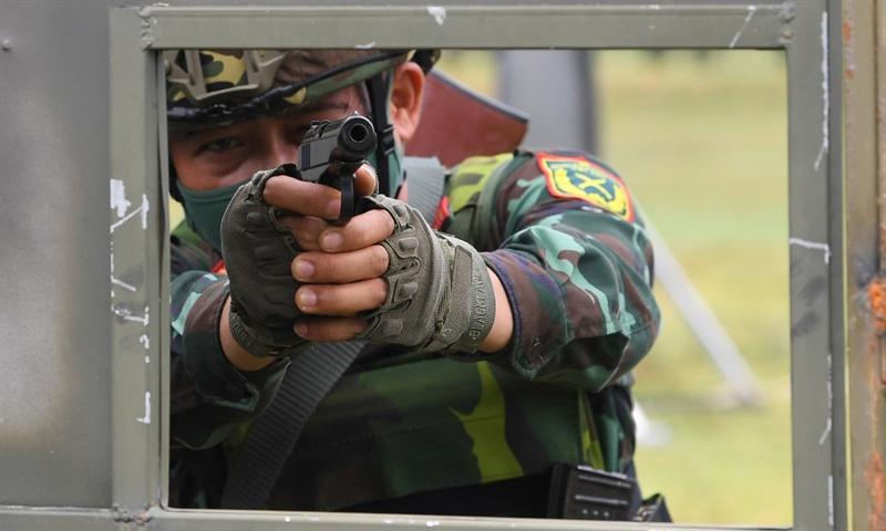 Xạ thủ súng quân dụng thực hiện nội dung bắn súng ngắn sau vật cản.
